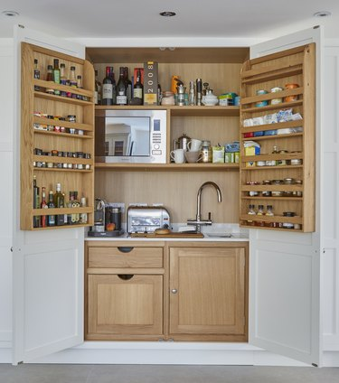 appliance garage meets pantry with sink, microwave and spice rack doors