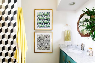 bohemian bathroom with pattern tile on accent wall and green vanity cabinet topped with plant