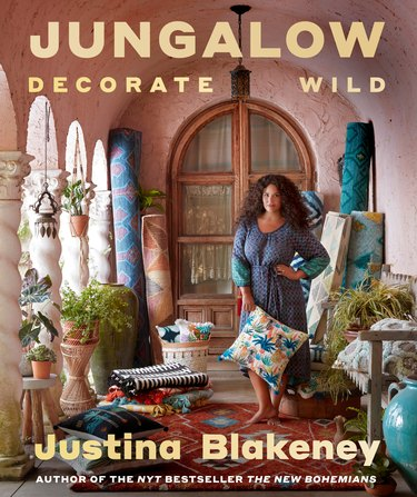 The cover of Jungalow, Decorate Wild, which shows Justina Blakeney wearing a blue dress and holding a pillow in a Bohemian entryway.