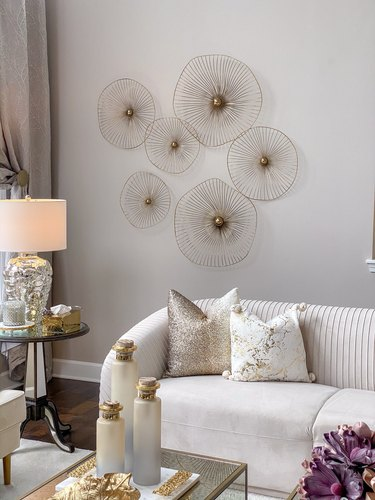 gold asymmetrical circle wall art behind white sofa