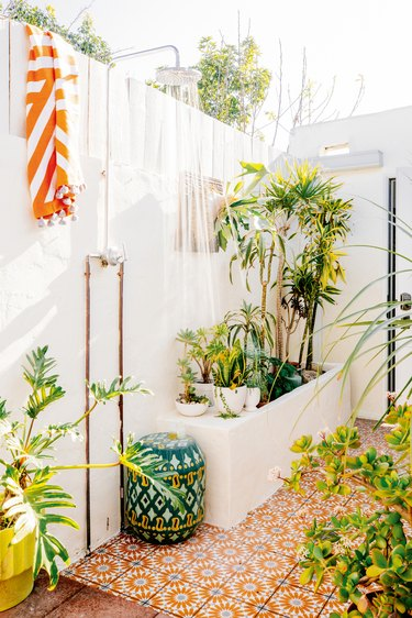 A white outdoor shower with blue and orange tile and tons of plants.