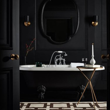 black bathroom walls with black clawfoot tub and black door