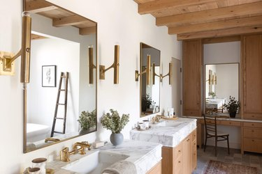 farmhouse bathroom with exposed wood beams at ceiling and stone flooring
