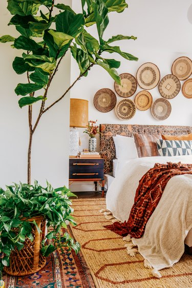A Bohemian bedroom with a wall of rattan decorations, plants, and a patterned headboard.