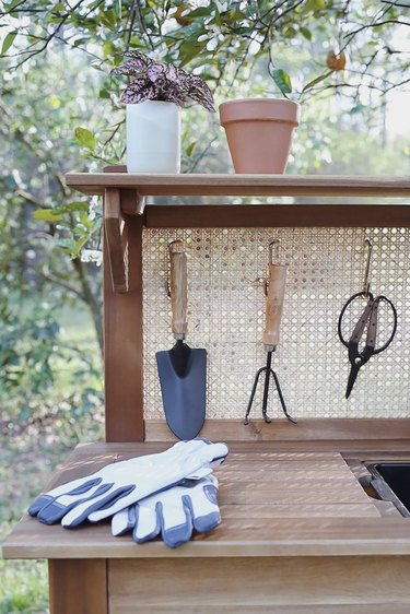 Garden tools hanging from hooks in the cane webbing