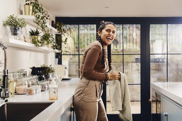 person laughing in kitchen with white counters and glass doors in the background