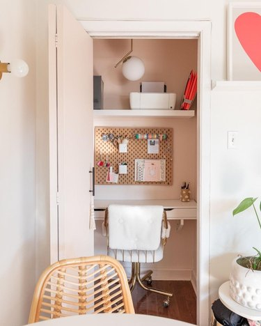 pink closet office with white swivel office desk and pendant light above