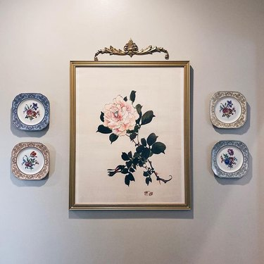 rose painting surrounded by small floral plates
