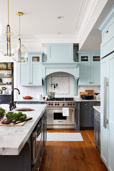 kitchen island sink in farmhouse space with blue cabinets and marble countertop
