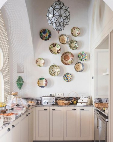 plates on kitchenette wall with high ceiling