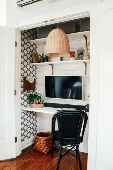 white closet office with woven pendant light hanging above, black desk chair