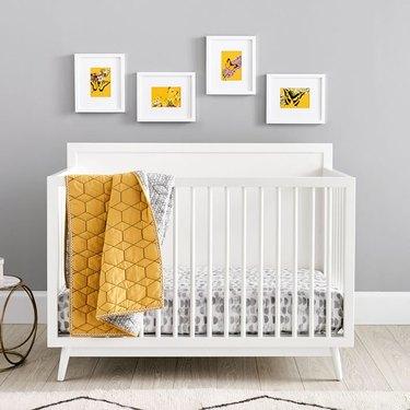 white crib with yellow blanket
