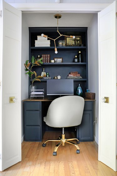 white closet office with black built-in desk and shelves with gray swivel chair