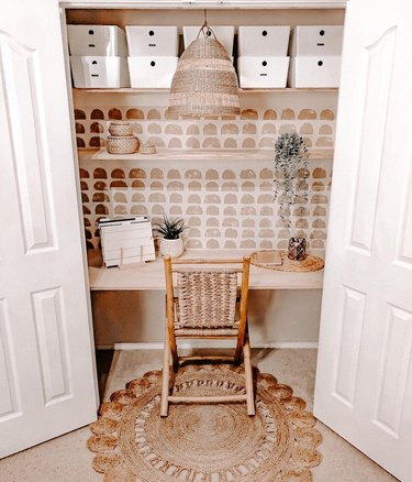 boho closet office with woven pendant lamp and chair, wallpapered accent wall