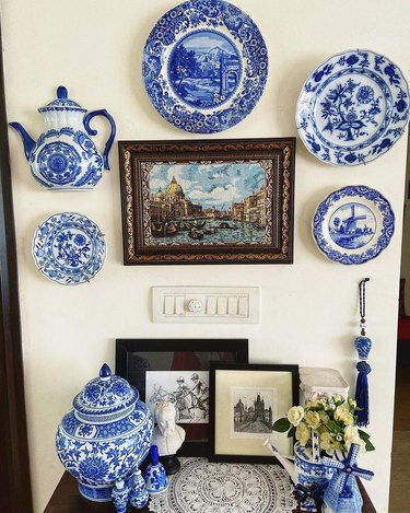 blue and white plates on wall next to decor table