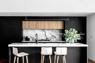 Modern kitchen island sink with black cabinets and marble countertop and backsplash