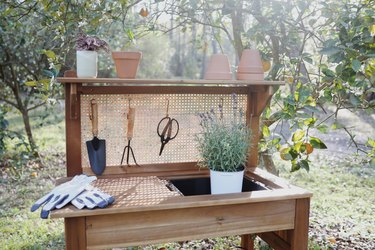 Potting bench with cane webbing stapled to back and garden tools hanging from cane webbing