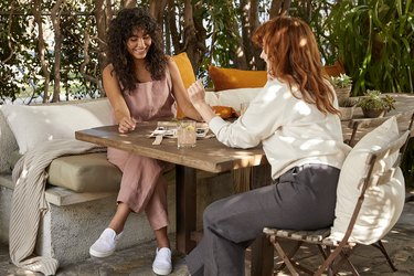 two women wearing linen loungewear at table