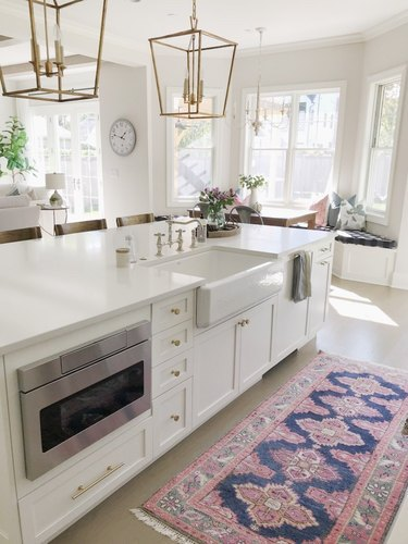 farmhouse kitchen island sink with white cabinets and brass pendant lights