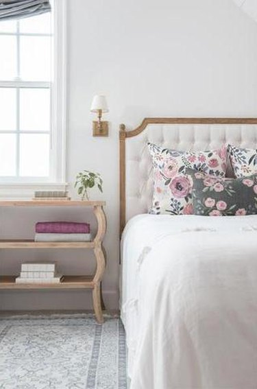 Farmhouse Chic Bedroom Ideas with decorative rug, table with shelves, bed with upholstered headboard