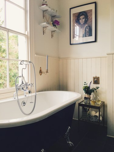 vintage farmhouse bathroom with tongue and groove walls and roll top bath