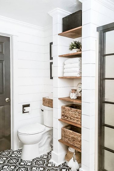 farmhouse bathroom with wooden shelving and black and white patterned floor