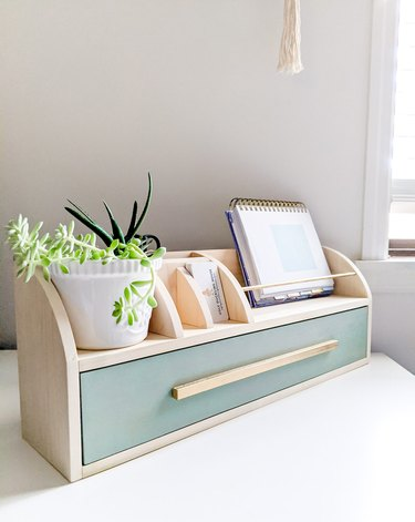 wood desk organizer with green drawer and small houseplant
