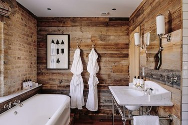 Bathroom with white tub and sink, reclaimed wood shiplap, brick wall.