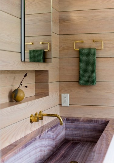 Bathroom sink area with light wood shiplap, pink marble sink.
