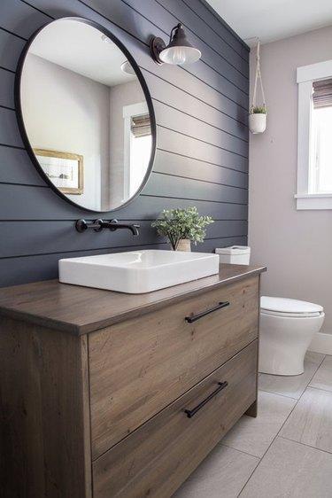 Gray shiplap wall in farmhouse style bathroom, wood vanity, round mirror.