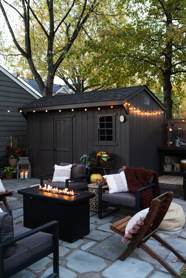 outdoor space with fire pit and chairs near shed in dark color with string lights and trees in the background