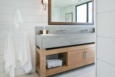 Bathroom with concrete sink, white shiplap walls.