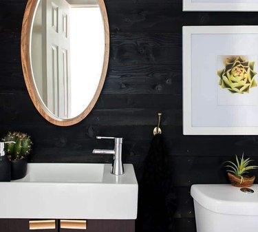 Bathroom with white sink, toilet, mirror, black shiplap walls.