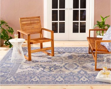 outdoor space with white door, wood chairs, and light blue patterned rug