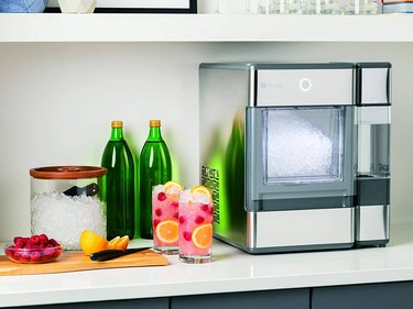 A freestanding nugget ice maker on a countertop next to sparkling water and two cocktails in tumblers