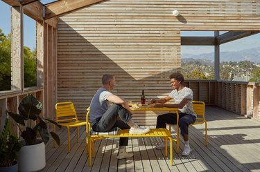 two people sitting outdoors in bright yellow furniture