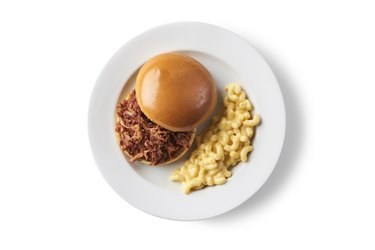 pulled pork sandwich and mac and cheese on white plate