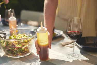 person holding squeeze bottle on table near salad bowl and wine glass