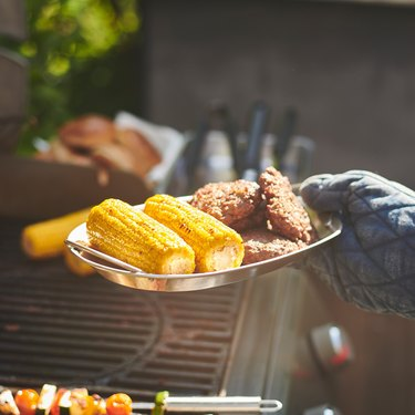 person holding a tray with corn and fried food near grill