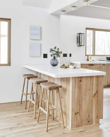 white kitchen with wooden detailed island and three flush mount light fixtures hanging above it