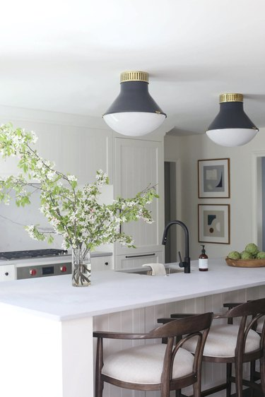 white kitchen with two gray and brass flush mount light fixtures