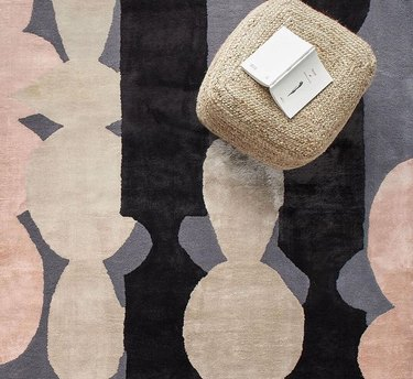 patterned multicolored rug with stool and book