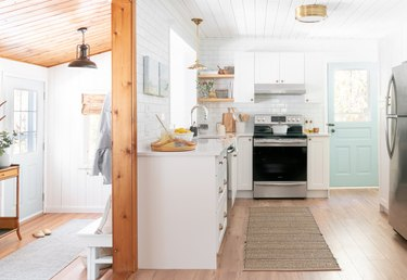 white kitchen with brass flush mount light fixture and a turqouise door
