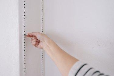 Removing shelf bracket clip from shelving track