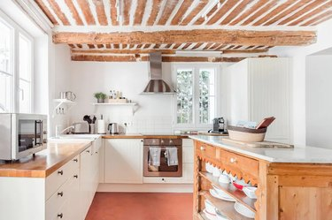 white french country style kitchen with exposed wooden beams