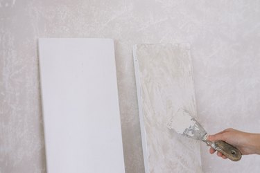 Applying Roman Clay to primed shelves with putty knife