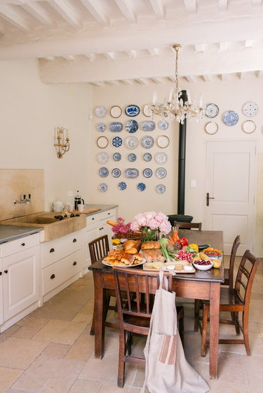 white french country style kitchen with wooden table in the center
