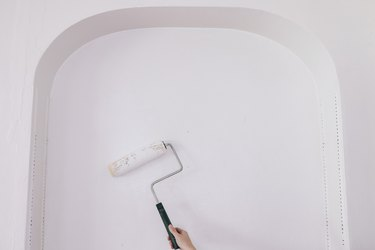 Rolling primer on built-in shelving wall with paint roller