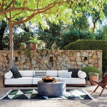 cb2 white outdoor sofa in backyard