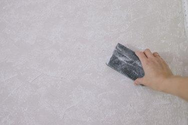 Sanding dried Roman Clay on wall